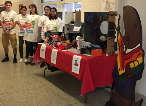 The Mole Day winners pose with their projects displayed. Ayden Cassano, Mya Ramos, Ashley Tolocka, Jake Vasquez, and Shayna Mangal received a glow in the dark T-shirt of a periodic table as their reward.