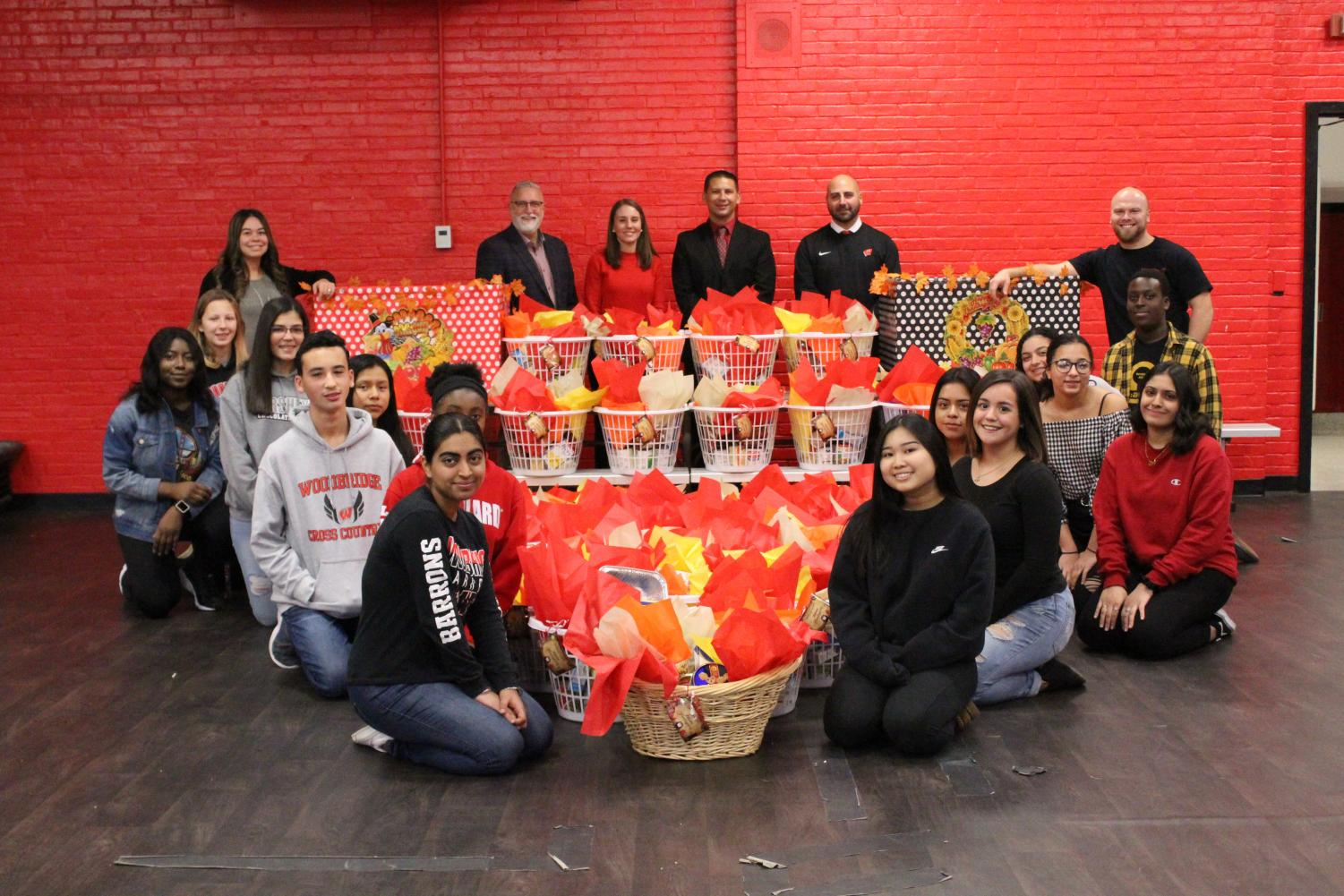 Interact Club poses with over two dozen donation packages. The club worked tirelessly for weeks to collect items to create the Thanksgiving baskets.