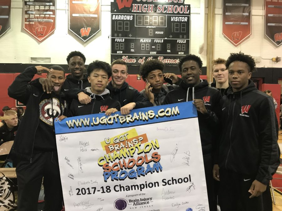 During the Winter School Prep Rally, the boys basketball team holds the U Got Brains banner to support safe driving.