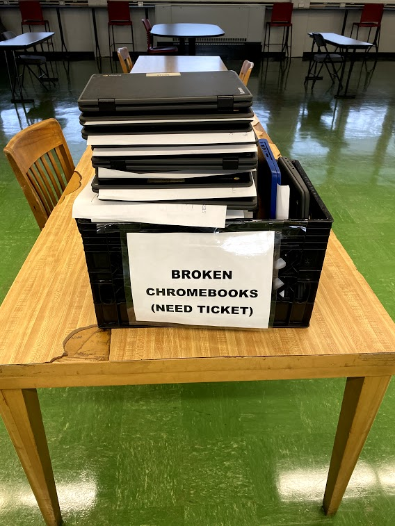 The virtual spring pep rally took a turn for the worse. Several broken Chromebooks were held in a crate, waiting to be shipped out for repairs.